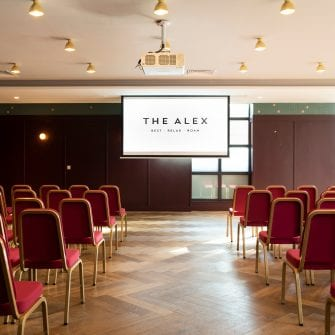 Screen and chairs set up for an event at The Alex Hotel